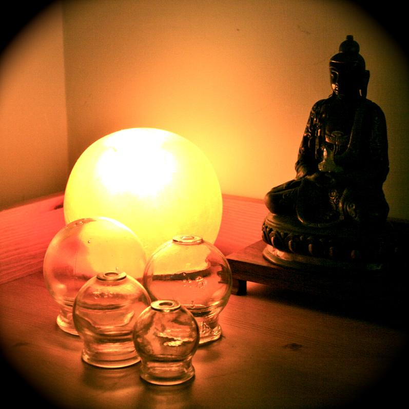 Statue of Buddha, surrounded by cupping for Traditional Chinese Medicine therapy. Globe light is on